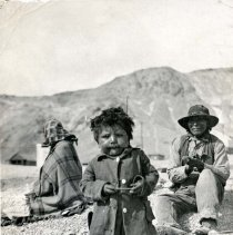 Image of UNRS-P2003-14-12 - A young brave. [Shoshone boy with his parents behind. View looks up toward the Tramp mine. Bullfrog, Nevada, ca. 1906. Photo by A. E. Holt?]