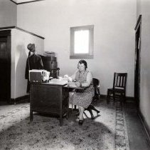 Image of UNRS-P1992-01-2071 - No id. [woman at desk in office, calendar page is May 1929]  Photo by Nevada Photo Service.