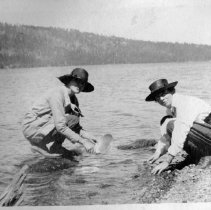 Image of UNRS-P1992-01-5297 - [Unidentified woman and man with camp stove. In album labeled Lake Tahoe scenes].