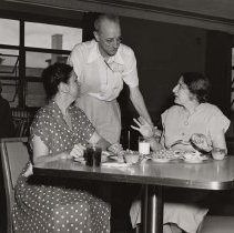 Image of UNRS-P1997-50-0714 - Image of a man conversing with two women eating. The man is leaning over the table between the two women. The women to the right is talking using hand gestures. The woman on the left is looking at her.
