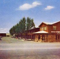 Image of UNRS-P1992-03-0703 - Postcard of Harolds Pony Express Motel. Caption on verso: Harold's Pony Express Motel No. 1. Entrance from U.S. 40, showing lobby in front. Each room has phone, radio, tile bath, beautifully furnished. Approved by AAA. Conveniently located. Quiet. Member United Motor Courts. [ca. 1955]