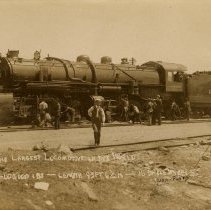 Image of UNRS-P1992-03-0820 - Postcard of workers surrounding a train with one man posing in the front. Caption on image: The Largest Locomotive in the World. Weight 600,000 lbs - Length 93 ft. 6 1/2 in. - 16 Drive Wheels. [ca. 1910]