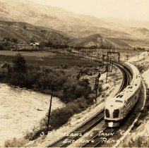"""Image of UNRS-P1992-03-0823 - Postcard containing photograph of train moving along Truckee River. Caption on image: S.P. Streamline Train """"City of San Francisco"""" entering Reno. [ca. 1940]"""