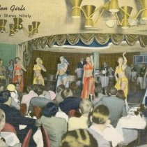 Image of UNRS-P1992-03-0386 - A colored photograph of several women on stage in different colored outfits dancing. The audience is filled with men watching. Caption on image: The Golden Girls. Complete Floor Shows Nitely. Caption on verso: The Golden Bank Casino, presenting in the Gold Room, the finest entertainment available and music 'round the clock. At the Casino Bar, four orchestras for your dancing pleasure. [ca. 1955]