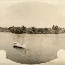 Image of UNRS-P1992-03-1191 - Image of Truckee River. Circa 1910. This image shows a small aluminum fishing boat anchored in the Truckee River. Trees and shrubs are bordering the river.