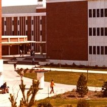 Image of UNRA-P2006-6 - A student walks near the Chemistry Building. The new Chemistry Building was built in 1970 in the center of campus in Barnes Plaza. The building houses a professional/student-run machine shop, a glass shop, and an electronics shop.