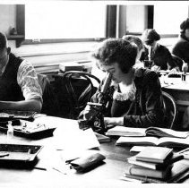 Image of UNRA-P641-46 - Women and men students look into microscopes during Biology Class (photograph album; photographic print, 4 x 7 inches).