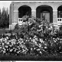 "Image of UNRA-P641-66 - Manzanita Hall is seen here in spring with surrounding flowers in full bloom with the caption on the image reading, ""Flower Bed, Manzanita Hall"" (photographic print, 4.75 x 7 inches). Manzanita Hall, originally known as ""The Cottage,"" was built in 1896 in an L-shape half the size it is today. In 1910 an addition and an eastern-facing porch were added, although the porch was removed when the building was remodeled in 1950. This was the second all-women dormitory built on the campus and maintains its women-only inhabitant policy today."