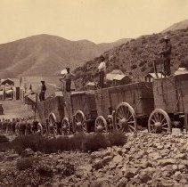 Image of UNRS-P0090-2 - Photograph of two views of ore wagons, used for hauling ore from mines to mills. Caption on image: Ore wagons, Nevada. From the George Wharton James collection