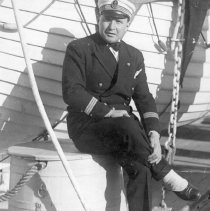 Image of UNRS-P1997-58-211 - Image of a man sitting on a bin on a dock next to a boat. He is wearing a navy uniform and is crossing is right leg over the left. Caption on image appears to be in French and illegible signiture, date 15 June 1936.
