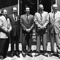 Image of UNRS-P2003-10-051 - Lee DeLauer, B.E. Lowe, and other unidentified men outside building.  February 15, 1960.
