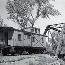 Image of UNRS-P1987-23-3688 - Photograph of Virginia and Truckee Railroad. Cleanup trains caboose with Truckee River bridge behind it, in Reno.
