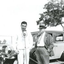 Image of UNRS-P1998-15-298 - [Jack Dempsey, speaking into KOH microphone; unidentified man, right; automobile in background]
