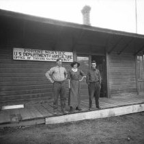 Image of UNRS-P2005-02-288 - Woman and two men standing on porch of Forest Service, U. S. Department of Agriculture, Office of Toiyabe National Forest; Austin? Ca. 1915]
