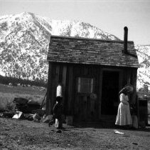 Image of UNRS-P2710-0332 - Photograph of woman and child in front of house; snow-covered mountains in background. Carson Valley. [Washo?]