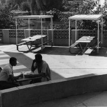 Image of UNRA-P2044-2 - Two students sit at a table outside of the JTSU. Manzanita Lake is visible in the background. The Jot Travis Student Union was built in 1958 as the first student center on campus. The building became home to the Davidson Academy when the new student center, the Joe Crowley Student Union, was opened in 2007.
