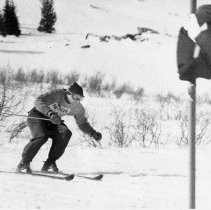 Image of UNRA-P3260-2 - An unidentified member of the Nevada Men's Ski Team skis past a flag during a race at the Pacific Coast Conference Winter Carnival. The Winter Carnival started on campus in 1939 and was an annual event where students participated in all kinds of winter activities, including skiing in the nearby Sierras, ice skating on Manzanita Lake, and electing Winter Carnival royalty. The event still happens on campus today, although in a much more tame version of free hot chocolate and carnival games. Circa 1955.