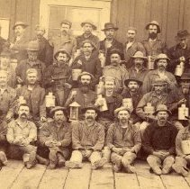 Image of UNRS-P0552-1 - Photograph of groups of workmen at the Gould and Curry Mine, taken about 1875. [Miners posing with lanterns and lunch pails] Photo by James H. Crockwell.