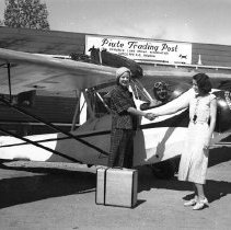 Image of UNRS-P2006-04-268 - [Two women shaking hands next to small airplane bearing Nevada Flying Club insignia; pilot in cockpit; Piute Trading Post, Pyramid Lake Indian Reservation sign in background; circa 1934] Best negatives 1931-32-33-34