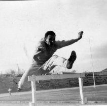 Image of UNRA-P1261-2 - An unidentified Nevada track and field team athlete jumps over a hurdle. (March 1949)