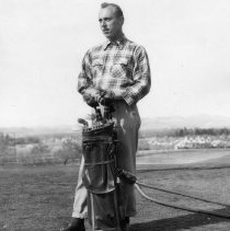 Image of UNRA-P1264-2 - Nevada golfer Stan Kosakawski stands next to his clubs while looking down the fairway. (April 1949)