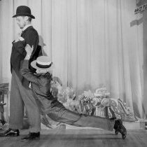 """Image of UNRA-P457-05 - Two men in suits act out a scene on stage. This theatrical production of """"The Psychoscope"""" presented on May 2, 1949 had the following student actors: George Bennet, Blythe Bulmer, Bob Burke, Norma Carmel, Bob Creveling, Robb Deady, Pat DeWalt, Helen Freil, Adele Frost, ? Hunt, Rex Jamison, Tusket Massing, Leo O'Brien, Lucille Parks, ? Pickering, Andrea Smart, Kenneth Stone, and Gerald Shyness."""