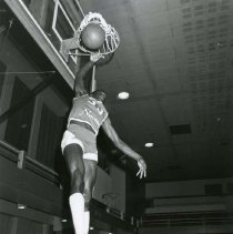 Image of UNRA-P887-1 - Photograph of Nevada men's basketball player Thaxter Arterberry dunking a ball during warm ups before a game in November, 1978. Arterberry was a forward for the Wolf Pack for the 1979 and 1980 seasons.
