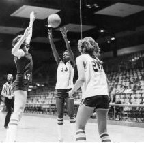 Image of UNRA-P900-3 - Women's basketball game against Warriors of California: unidentified players and referee, wih ball in the air (1980)