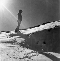 Image of UNRA-P941-04 - Photograph of unidentified person standing on a snowy hill, with footprints in the foreground (circa 1980).