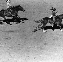 Image of UNRS-P1420-1 - Photograph of two Indians riding horses in Reno Rodeo, July 4th [ca. 1930s-1950s]