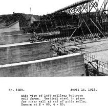 Image of UNRS-P2008-18-3645 - Side view of left spillway buttress wall forms. Vertical steel in place for riser wall at end of guide walls. Camera at M + 00, 4 + 20. April 16, 1913.