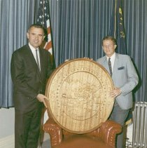 Image of UNRA-P3426-0500 - Governor Paul Laxalt and Art Professor Craig Sheppard stand with a replica of the Nevada State Seal that Sheppard carved in mahogany. The seal was hung in the Governor's office in Carson City, Nevada (color photograph). (June 1967)