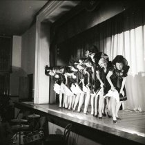 "Image of UNRA-P457-13 - Women actresses lift up their ruffled skirts to show off their legs during this dance scene. This theatrical production of ""The Psychoscope"" presented on May 2, 1949 had the following student actors: George Bennet, Blythe Bulmer, Bob Burke, Norma Carmel, Bob Creveling, Robb Deady, Pat DeWalt, Helen Freil, Adele Frost, ? Hunt, Rex Jamison, Tusket Massing, Leo O'Brien, Lucille Parks, ? Pickering, Andrea Smart, Kenneth Stone, and Gerald Shyness."