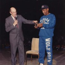 Image of UNRA-P3188-1 - Photograph of University President Joseph Crowley presenting award to Bill Cosby, who is dressed in blue Wolf Pack sweats. A donation from Cosby enabled the University to acquire an indoor track, which is housed at the Reno Livestock Events Center.  (March 16, 1991).