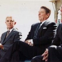 Image of UNRA-P3258-5 - President Ronald Reagan's visit to UNR: Senator Paul Laxalt, President Ronald Reagan, and Governor Robert List seated together, with an unidentified man in the background (October 7, 1982).