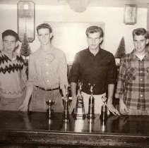 Image of UNRA-P3427-0057 - Four fraternity members stand at a table with trophies. (1930s)