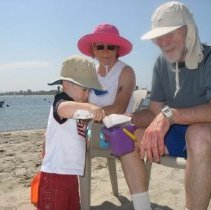 Image of UNRA-P3472-040 - Peggy and Milt Glick with a grandchild at a beach (circa 2008).
