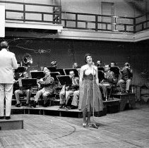 Image of UNRA-P3475-0117 - Photograph of Felton Hickman, Sr., conducting the University of Nevada band with an unidentified female singer in the old Gymnasium (1896). 3rd from right with flute: Orville Fleming.  .