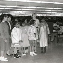 Image of UNRA-P429-10 - Photograph of unidentified women and Native American girls standing near a study area on the main floor of Getchell Library during a tour sponsored by the YWCA. Circa 1960s.