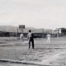 Image of UNRA-P484-041 - Four unidentified students play tennis with the Mackay Training Quarters in the background.