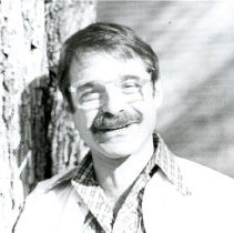 Image of UNRA-P782-1 - Photograph of Howard Rosenberg, Art Department, next to a tree trunk (1979).