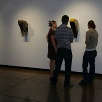 Image of UNRA-P3601-00205 - Photograph of three unidentified people viewing artwork in Sheppard Gallery.