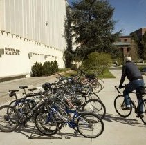 Image of UNRA-P3601-00460 - Student rides his bike to class, outside Mack Social Science