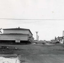 """Image of UNRA-P1804-01 - Photograph of the southeastern corner of """"Victory Heights,"""" on the UNR campus. Married student housing for military veterans and their families, with parked cars. A railroad crossing sign and tracks are in the foreground."""