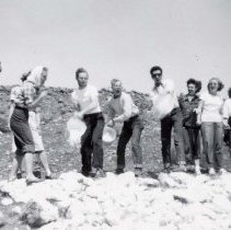 """Image of UNRA-P3571-04 - Photograph of unidentified students watching two boys throwing buckets of paint onto the """"N"""" on Peavine Mountain (ca. 1945)"""