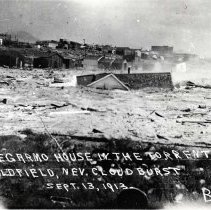 Image of UNRS-P1196-1 - Photograph of Goldfield Nevada. Caption on image: Degarmo House in the torrent. Goldfield, Nev. Cloudburst Sept. 13, 1913.