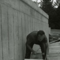 Image of UNRA-P1075-56 - Photograph of unidentified workman during construction of campus sign (1960s)
