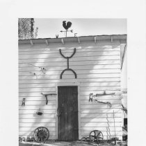 Image of UNRS-P2003-13-025 - Photograph of the exterior wall of a shed with a rooster weather vane on the roof
