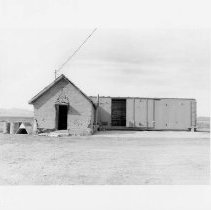 Image of UNRS-P2003-13-195 - Photograph of an adobe building with a boxcar, Reed's Ranch, Paradise Valley. View of an adobe building with a railroad boxcar in the rear; photograph taken September 15, 2002.