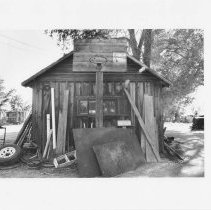 Image of UNRS-P2003-13-354 - Photograph of a basketball hoop mounted on the exterior of a blacksmith shop, Scierini Ranch, Yerington.